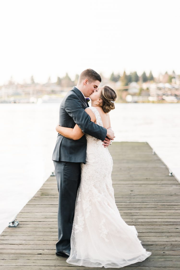 Mackenzie & Kellen, a client of Fortnight Photo, hold each other and sharing a kiss on a dock that looks out on a lake.