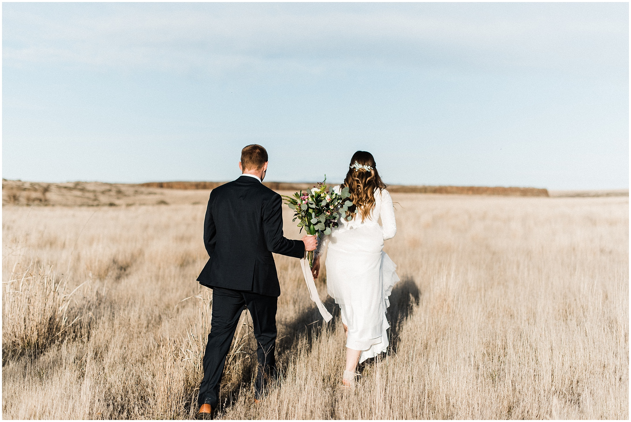 Photo of a bride & groom walking through a field by Forthright Photo