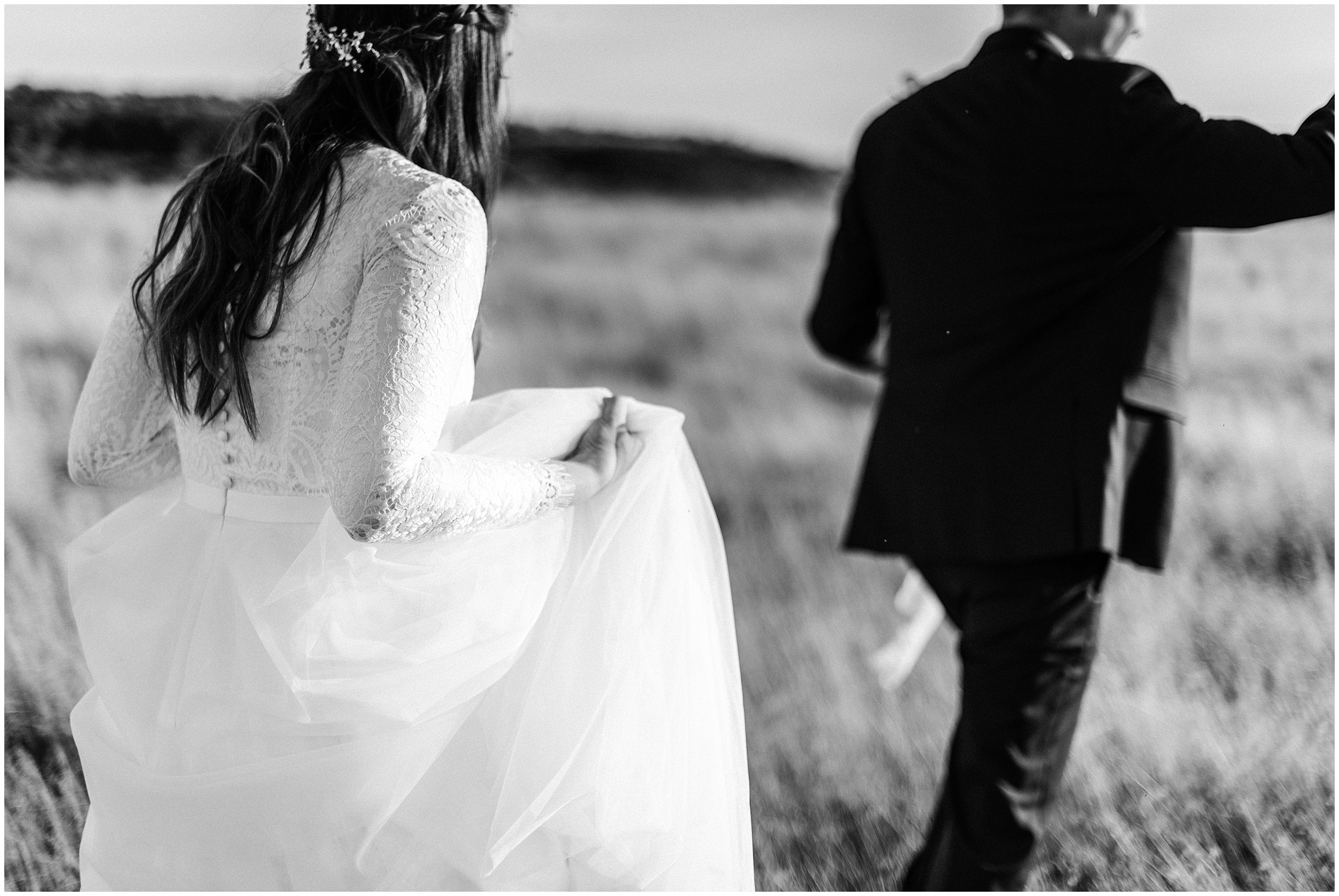 Black and white photo of a bride and groom walking by Forthright Photo