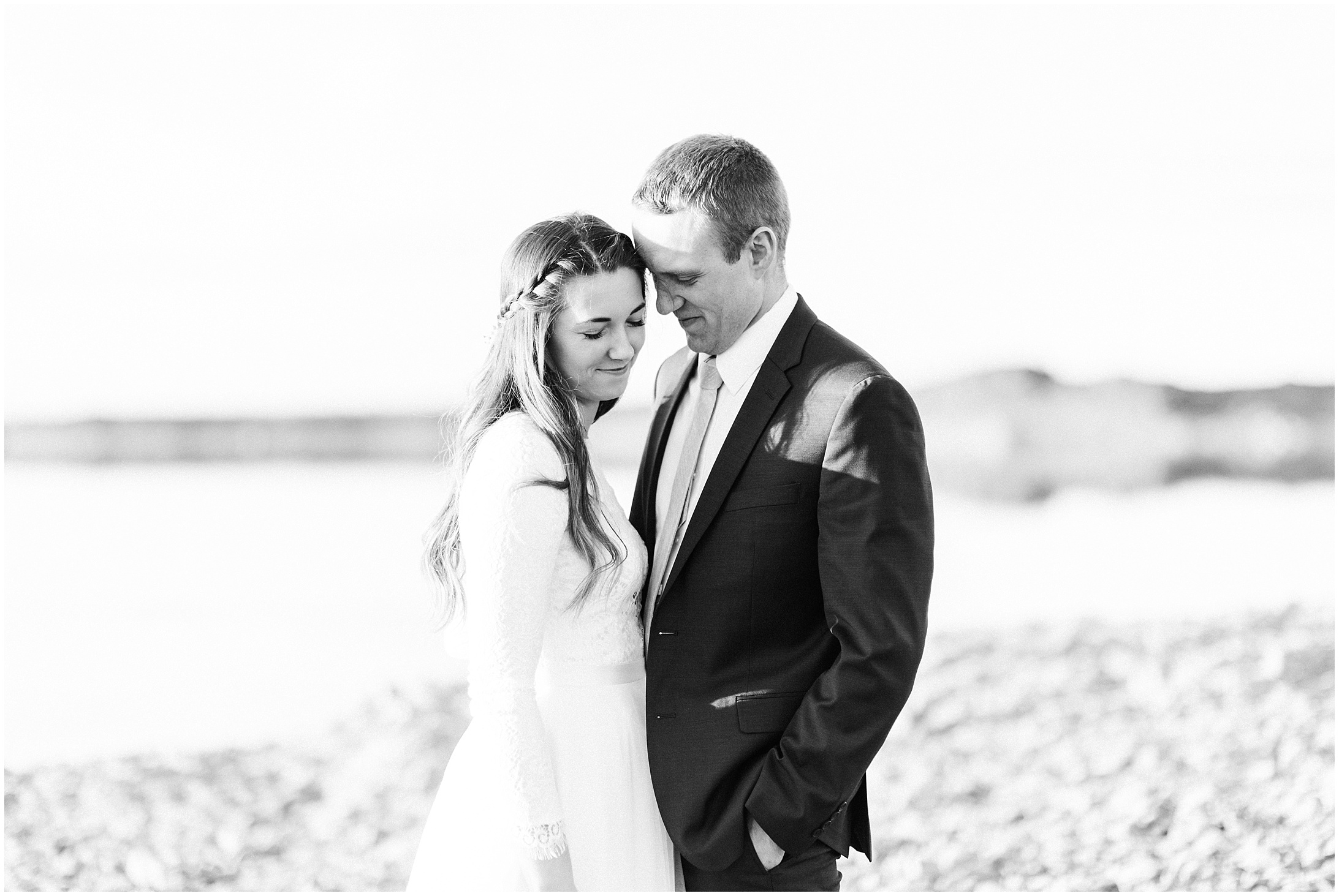 Black and white photo of a bride and groom standing by a desert lake by Forthright Photo