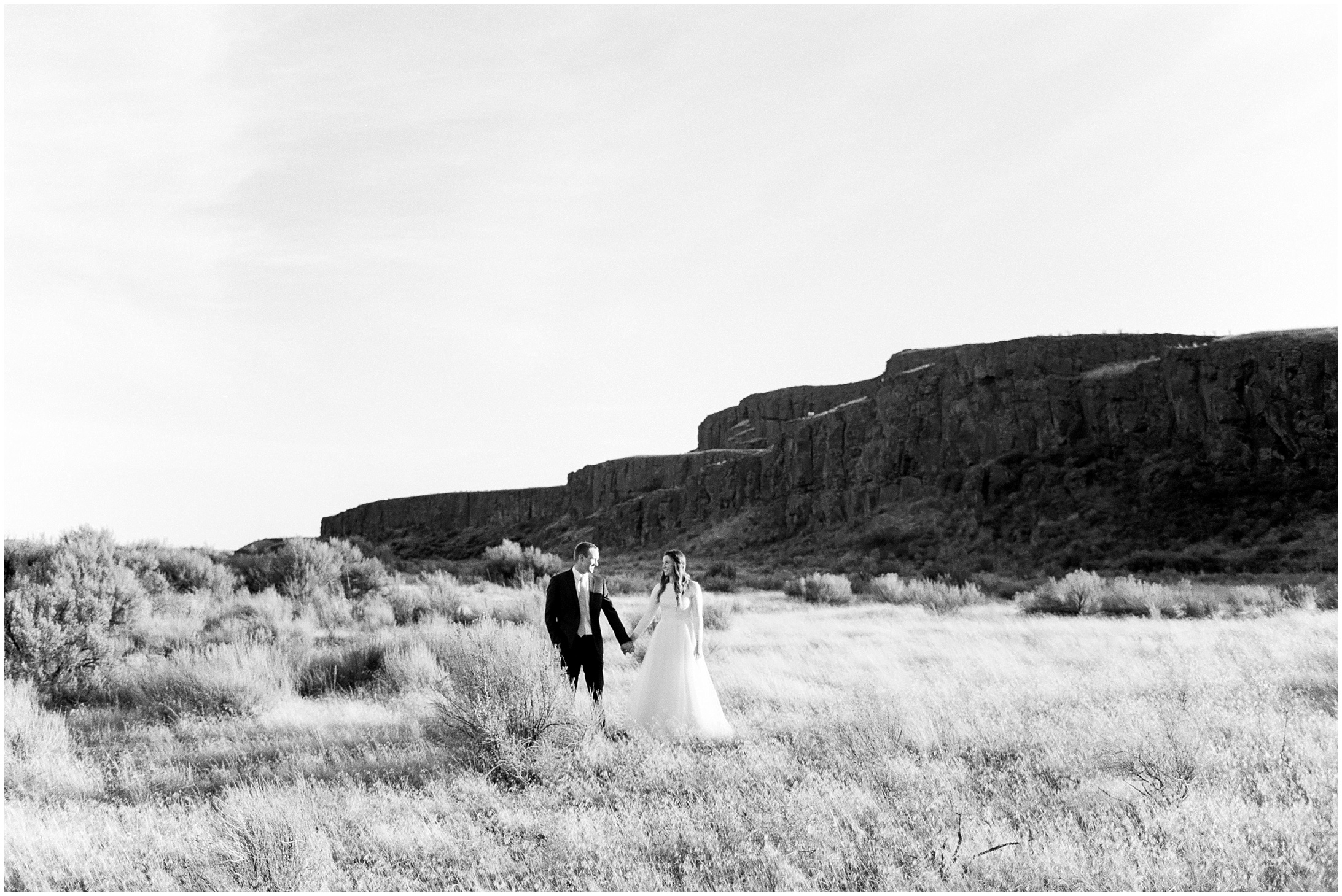 Photo of a bride & groom standing in a field by Forthright Photo