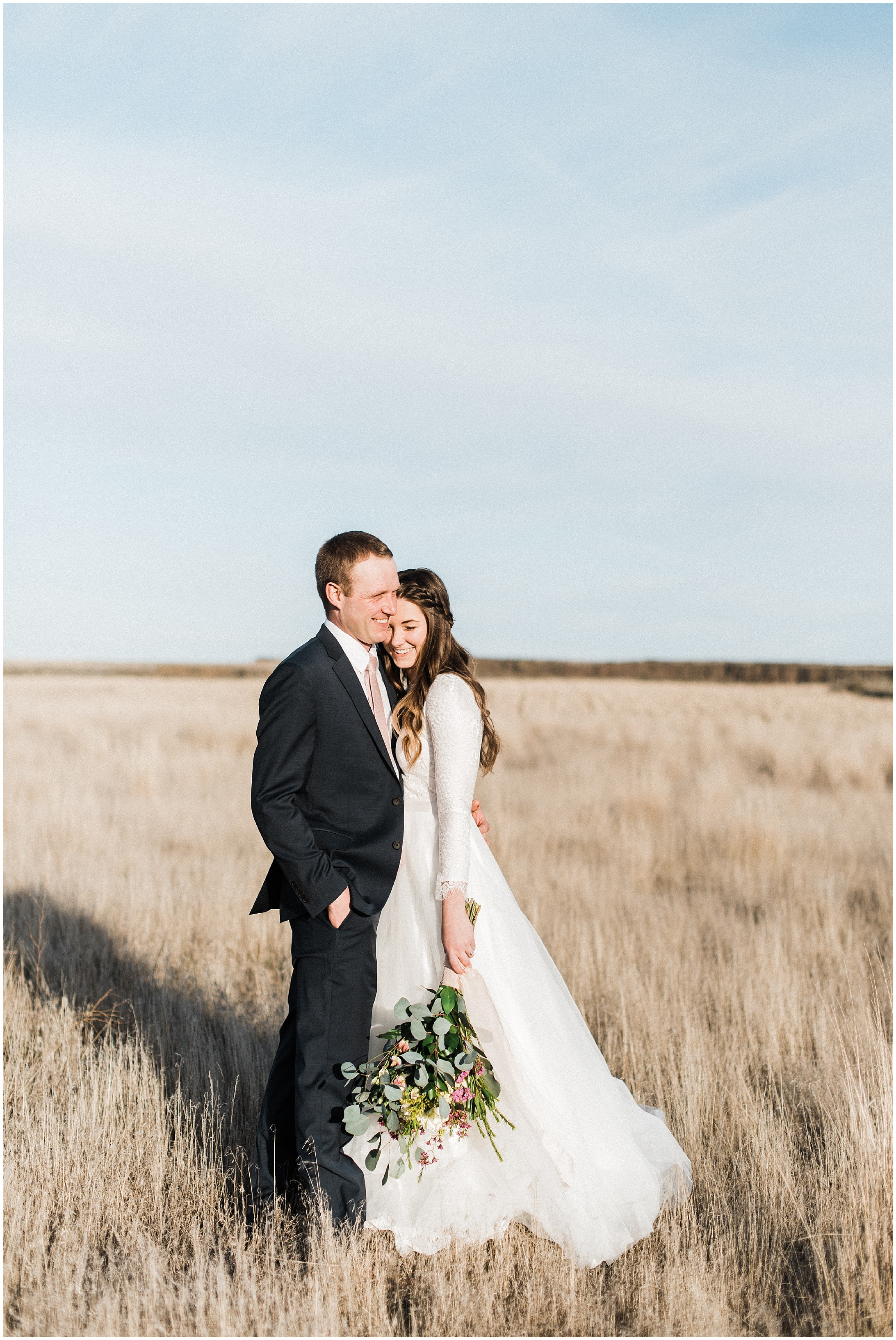 Photo of a bride & groom standing a field by Forthright Photo