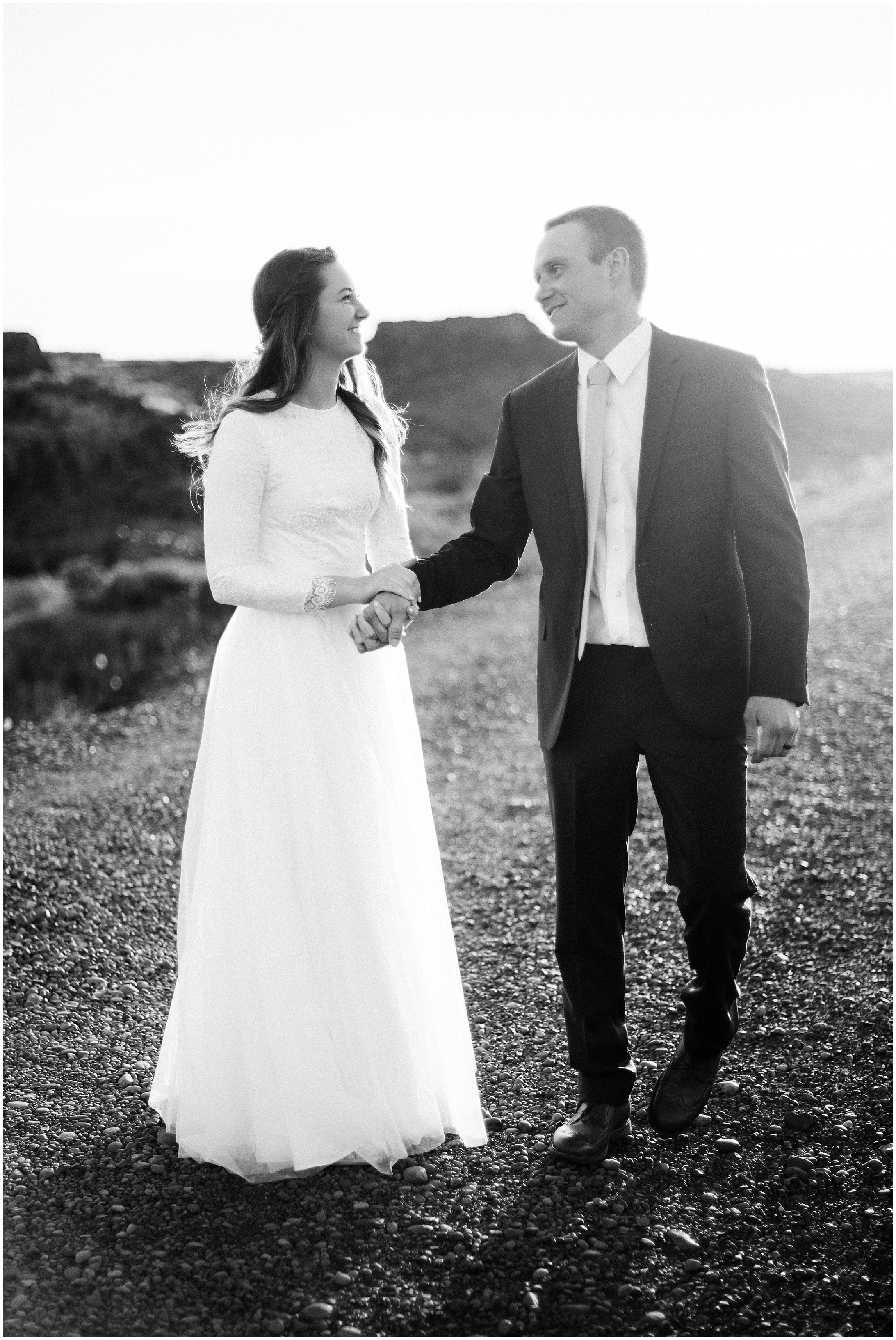 Black and white photo of a bride and groom walking along a road by Forthright Photo