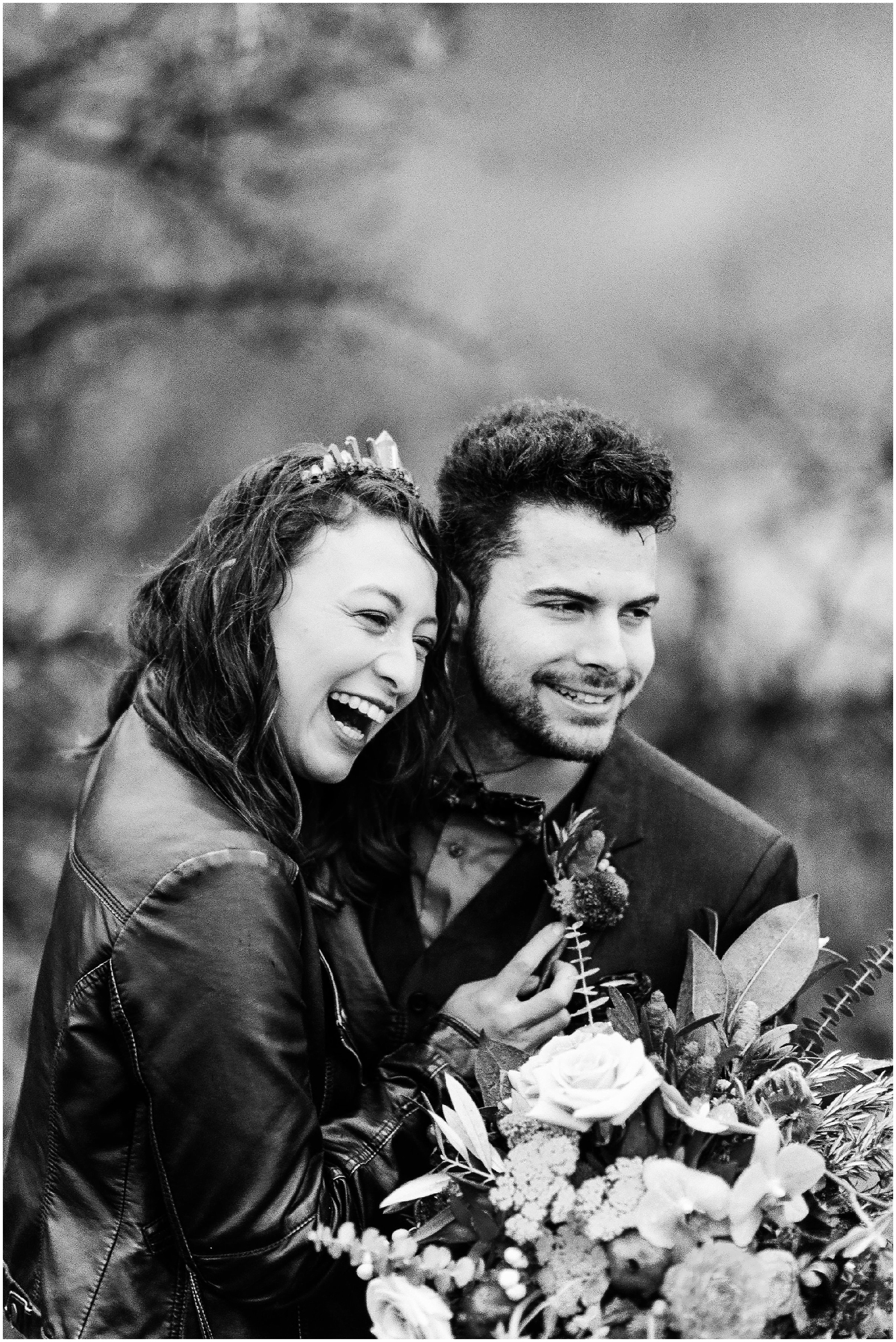 Black and White photo of a bride and groom laughing in the rain by Forthright Photo