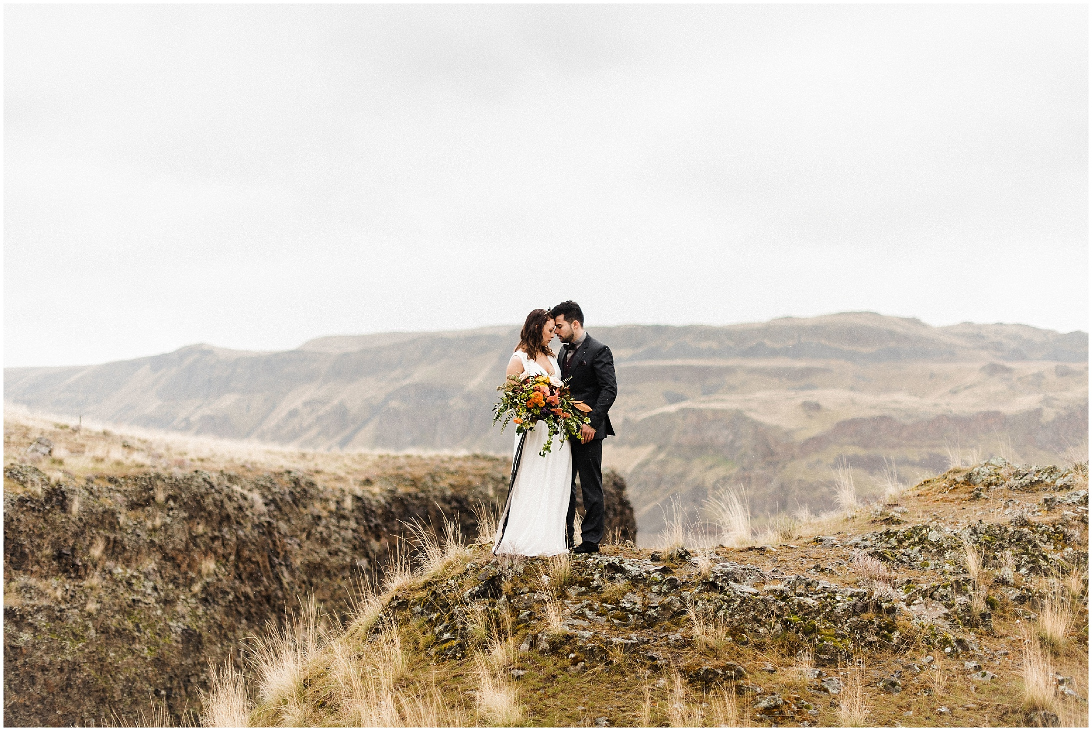 Photo of bride and groom standing on a cliff in a styled elopement at Lyon's Ferry State Park by Forthright Photo
