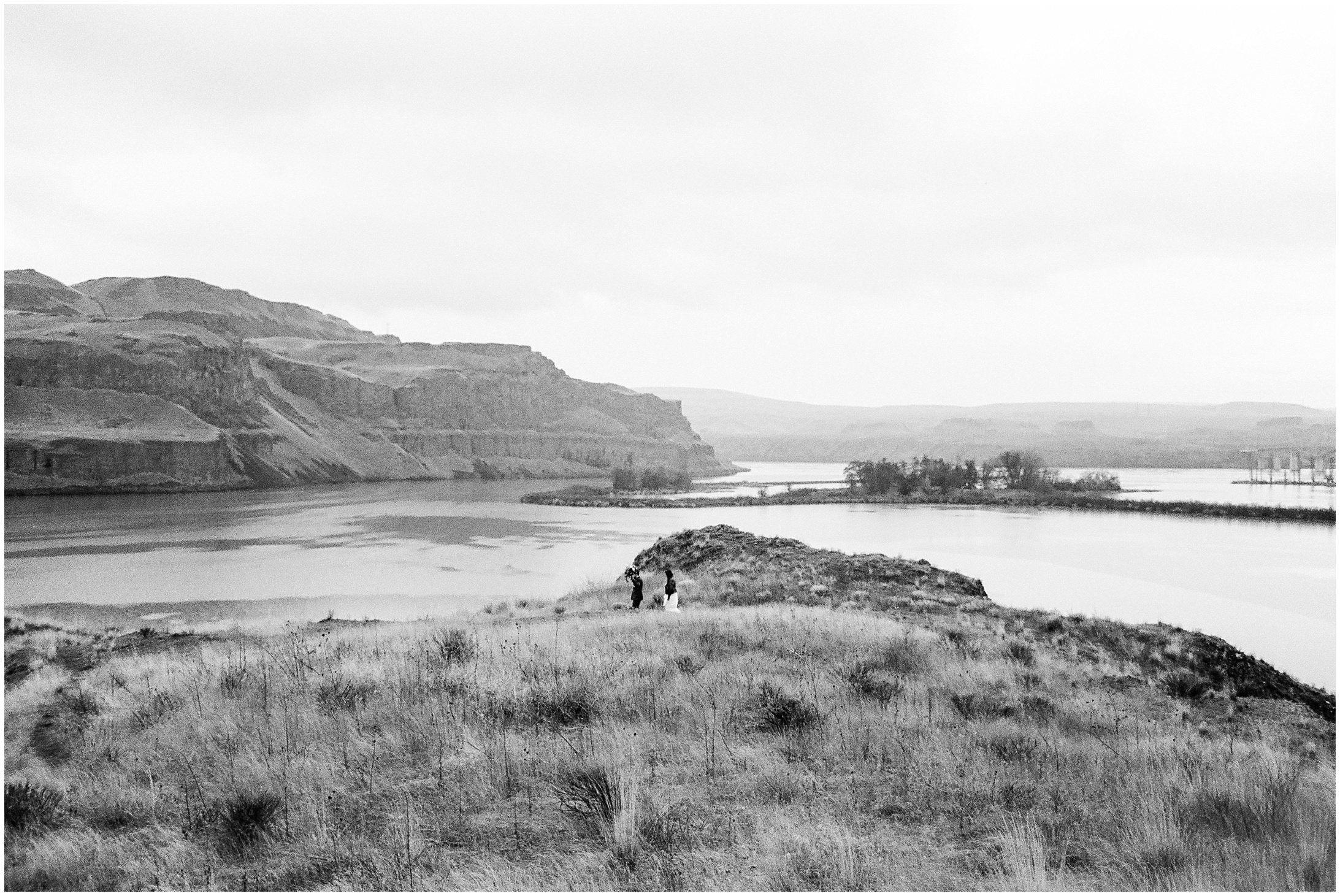 Black and white wide landscape photo of a bride & groom walking in the rain at Lyon's Ferry State Park by Forthright Photo