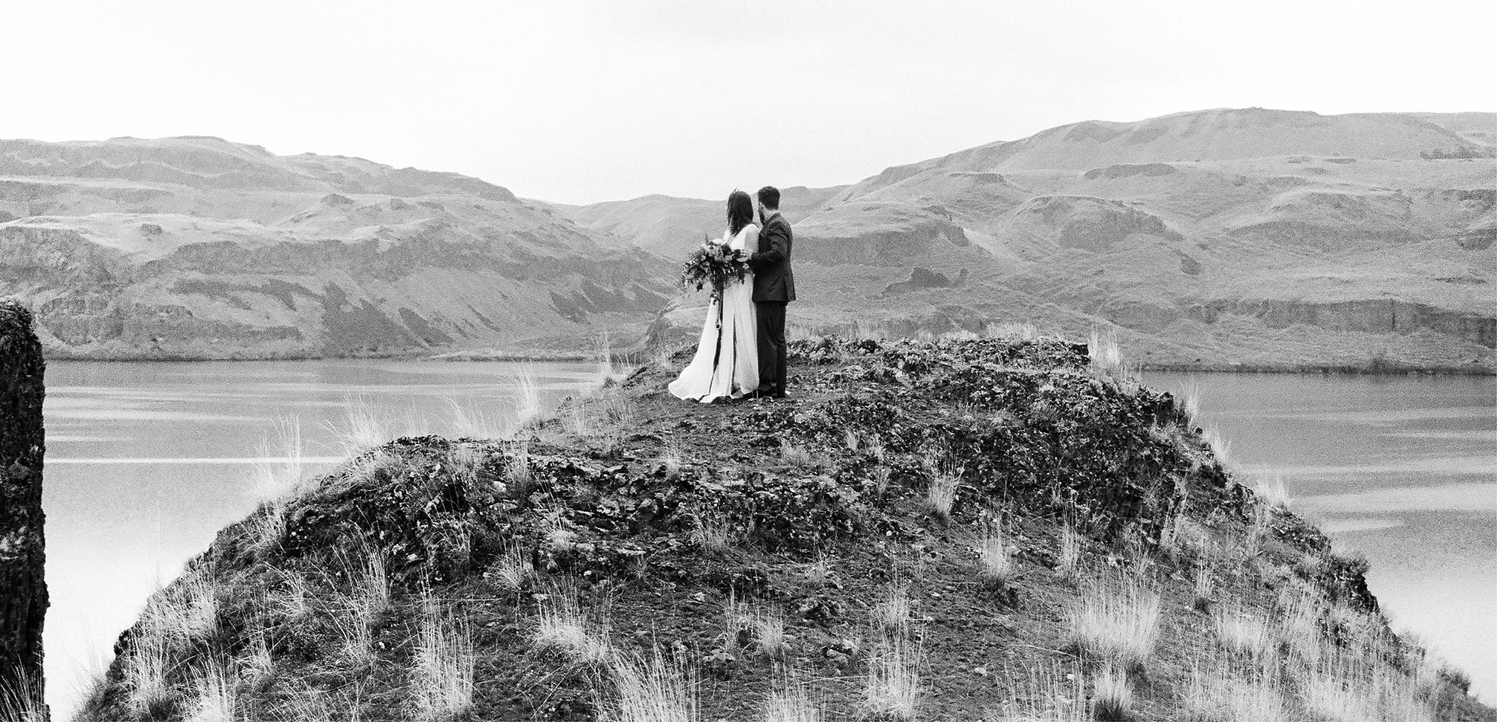 Black and White photo of bride and groom standing on a cliff in a styled elopement at Lyon's Ferry State Park by Forthright Photo, Oregon Wedding Photographers