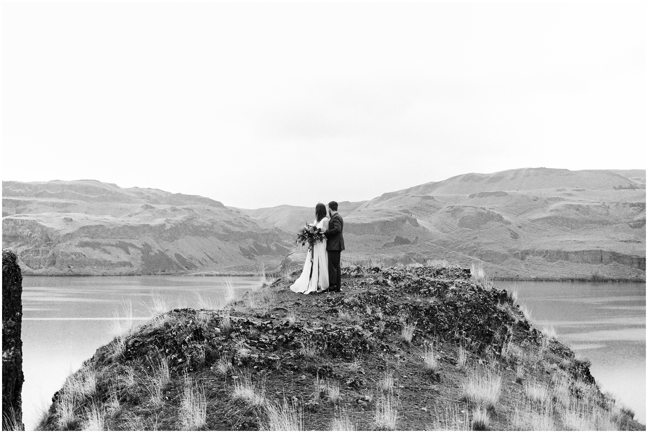Black and White photo of bride and groom standing on a cliff in a styled elopement at Lyon's Ferry State Park by Forthright Photo