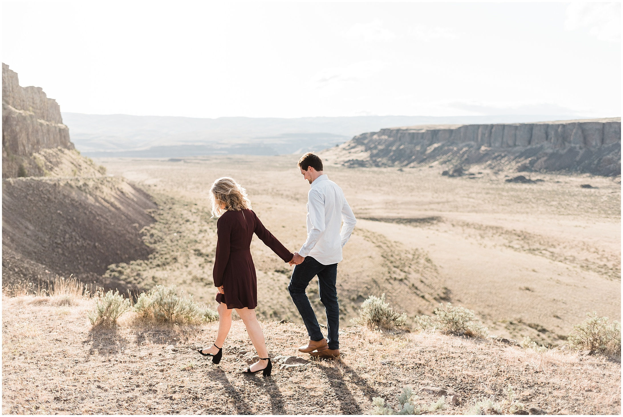 Photo of a couple walking alongside a desert canyon edge in in Vantage WA by Forthright Photo