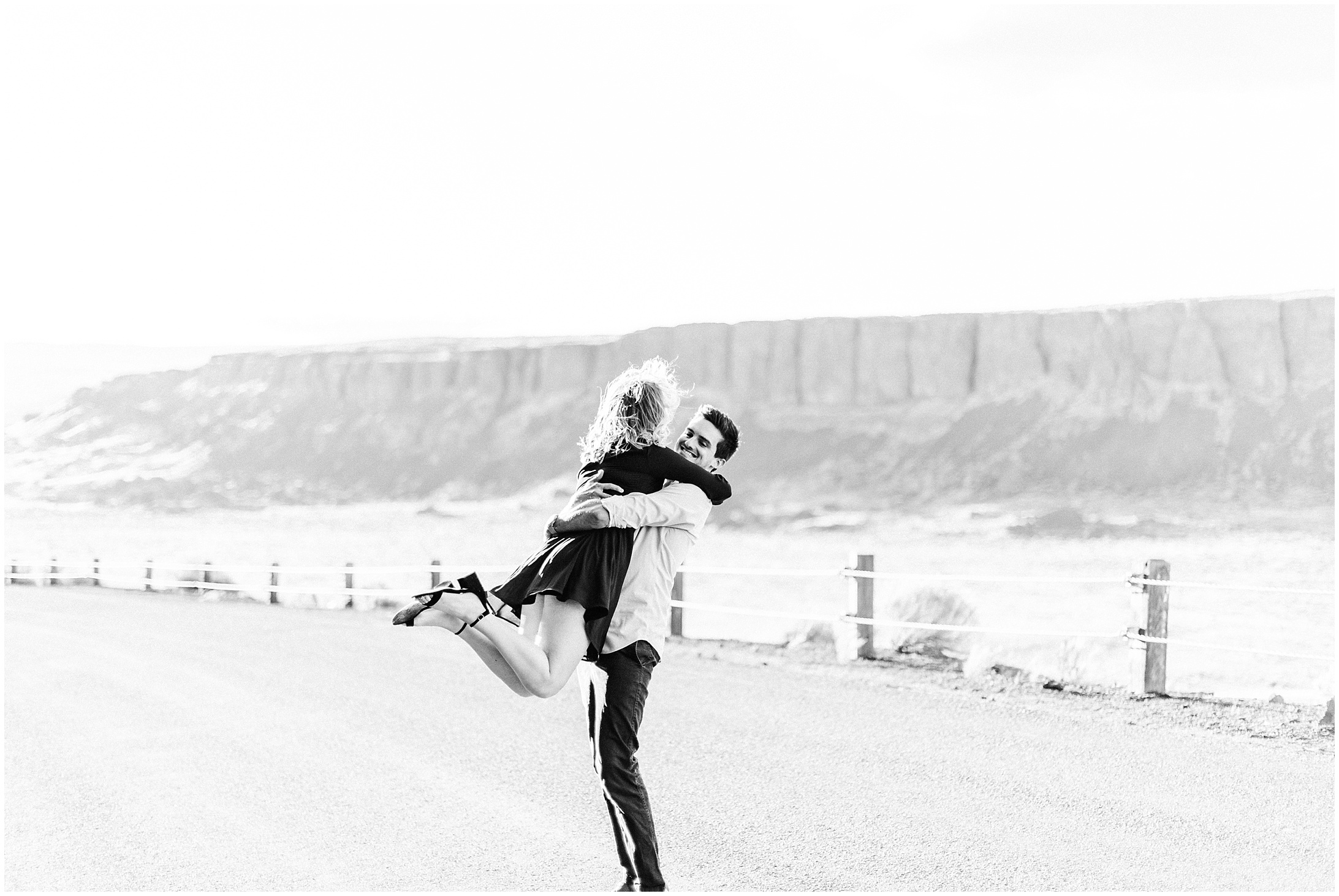 Black and White photo of a couple dancing alongside a desert road by Forthright Photo