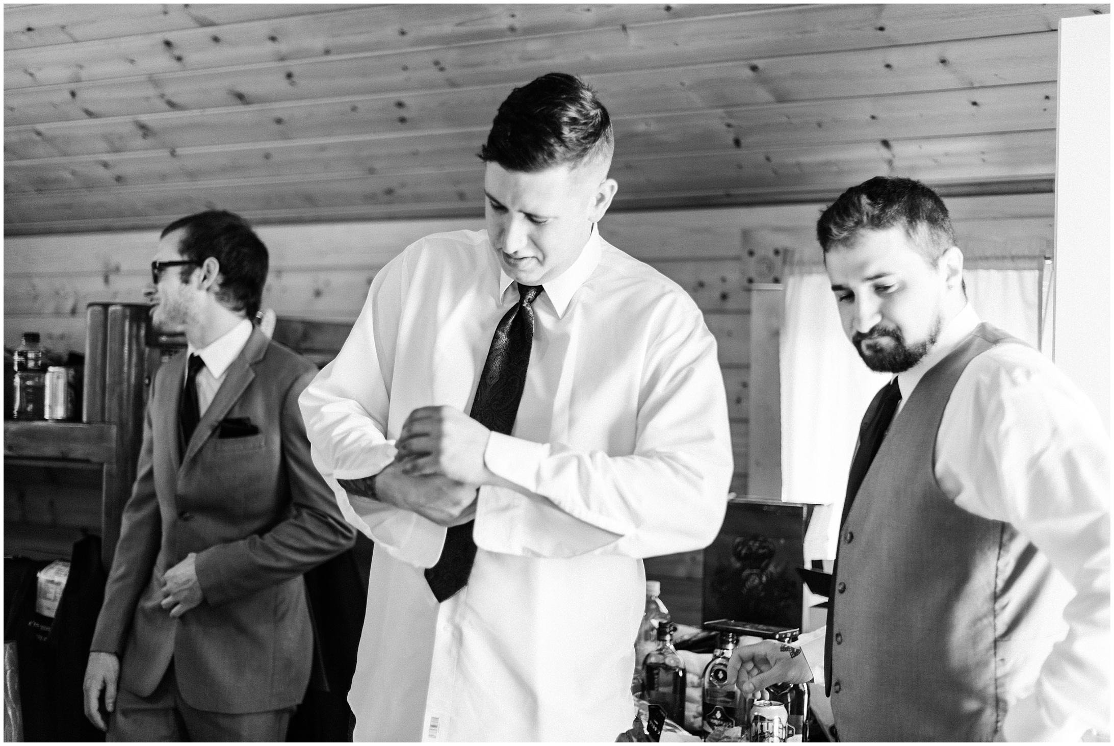 Black and White photo of a groom buttoning his shirt