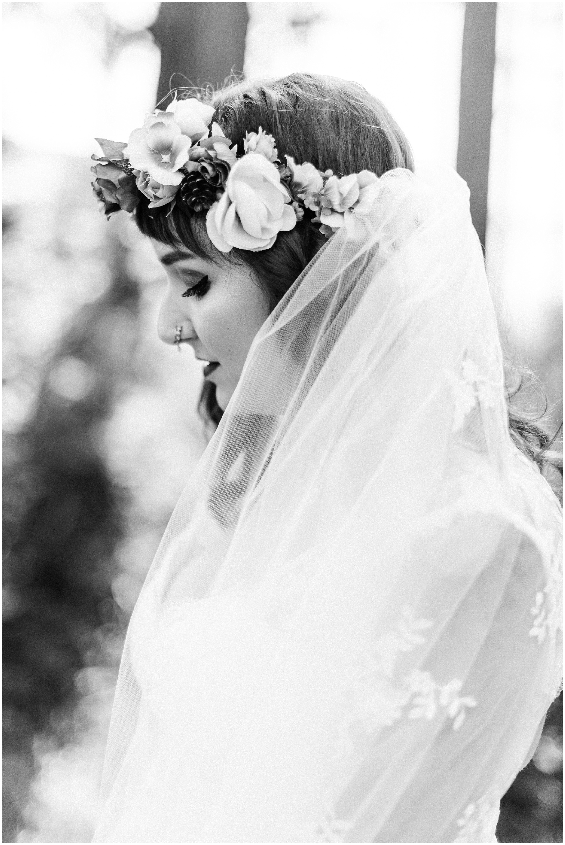 Black and white photo of a bride with her veil blowing in the wind