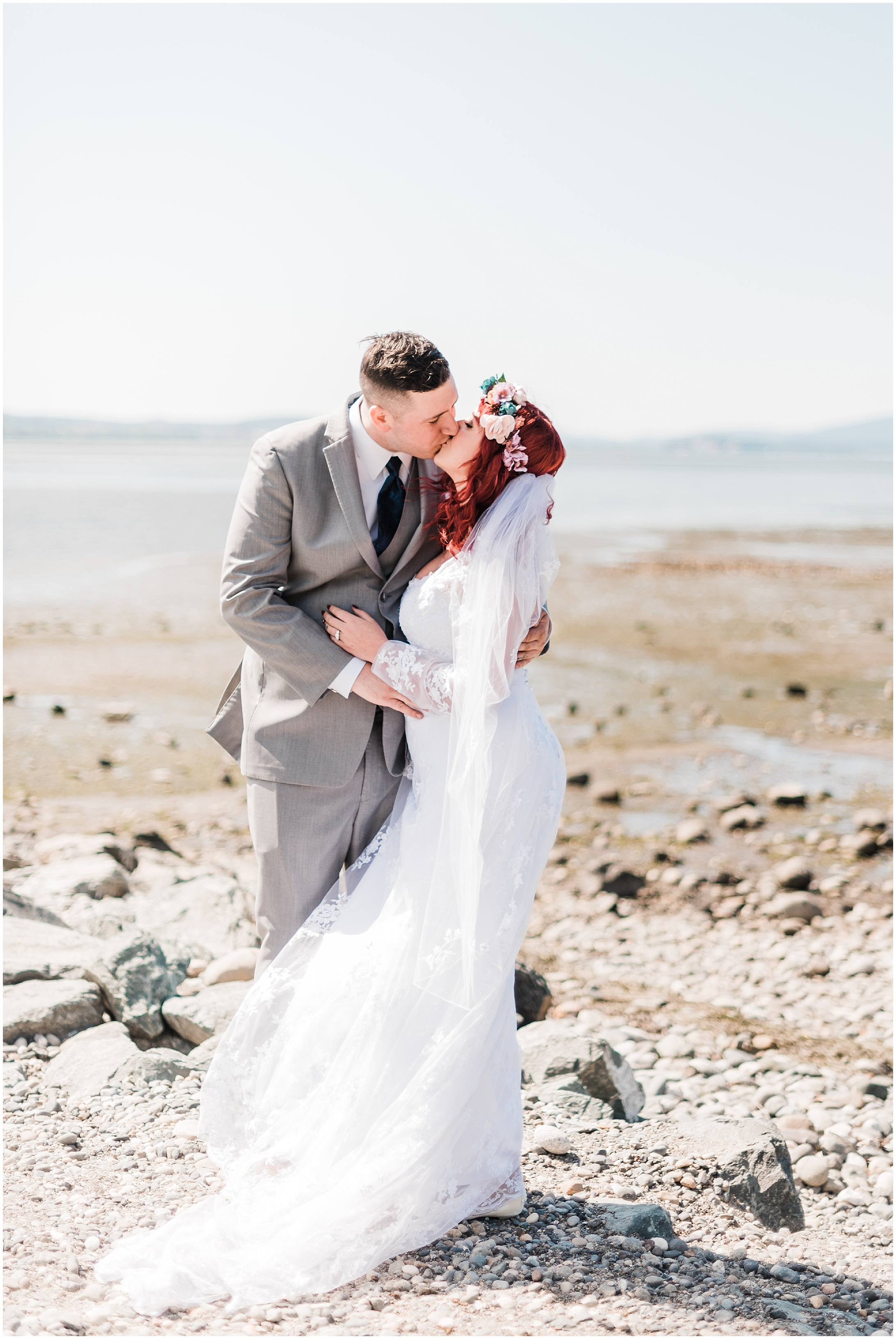 Photo of a bride and groom kissing on a windy, rocky beach at low tide
