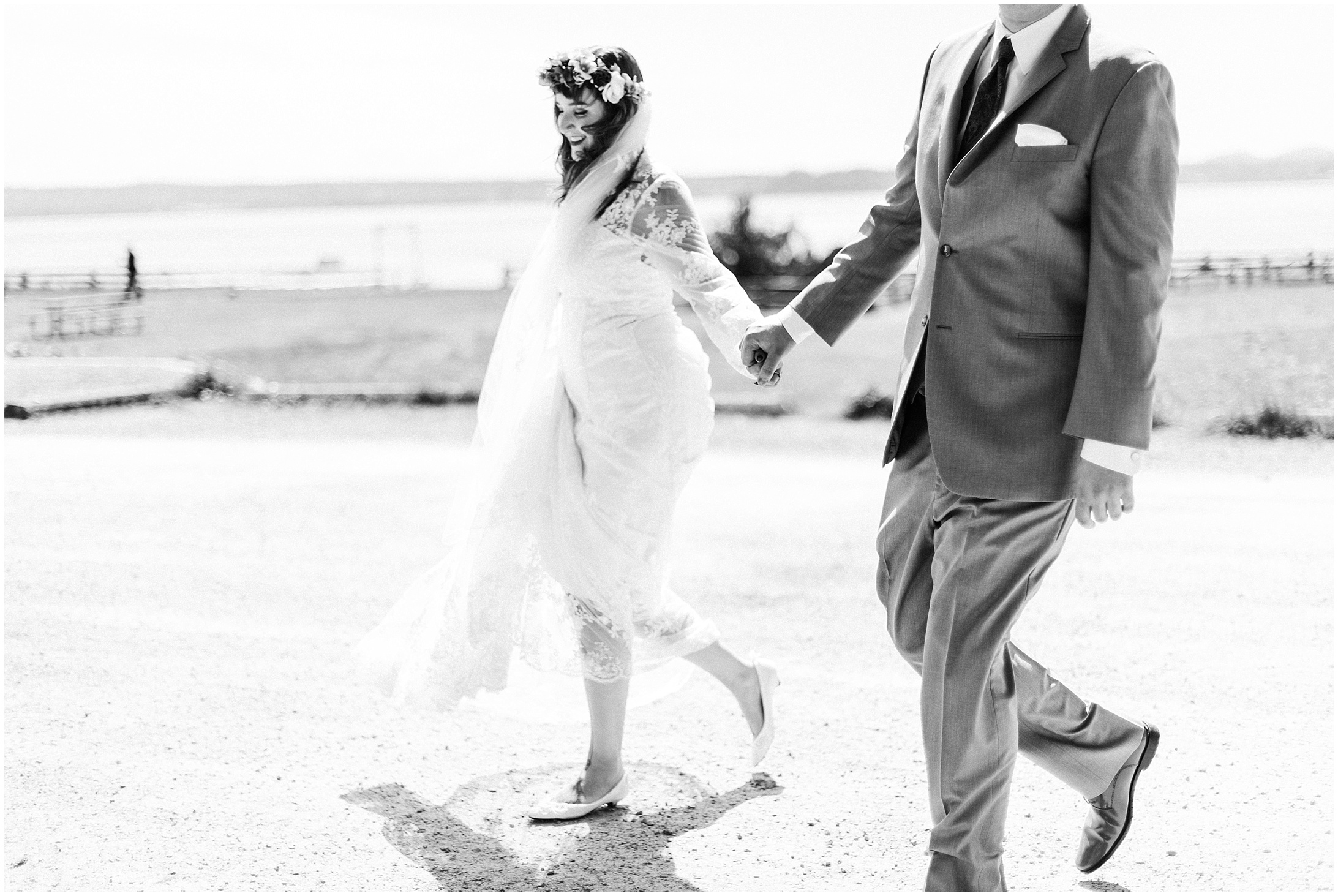 Black and white photo of a bride and groom walking along a windy stretch of road