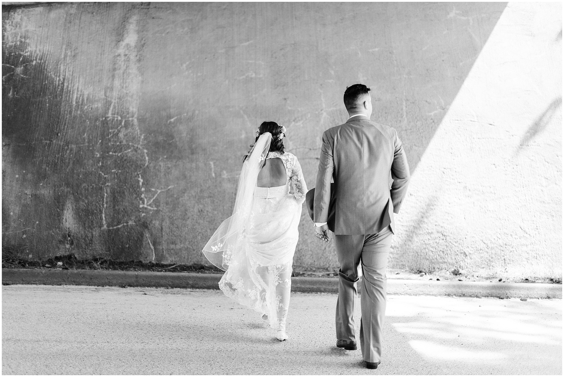 Black and white photo of a bride and groom in an underpass