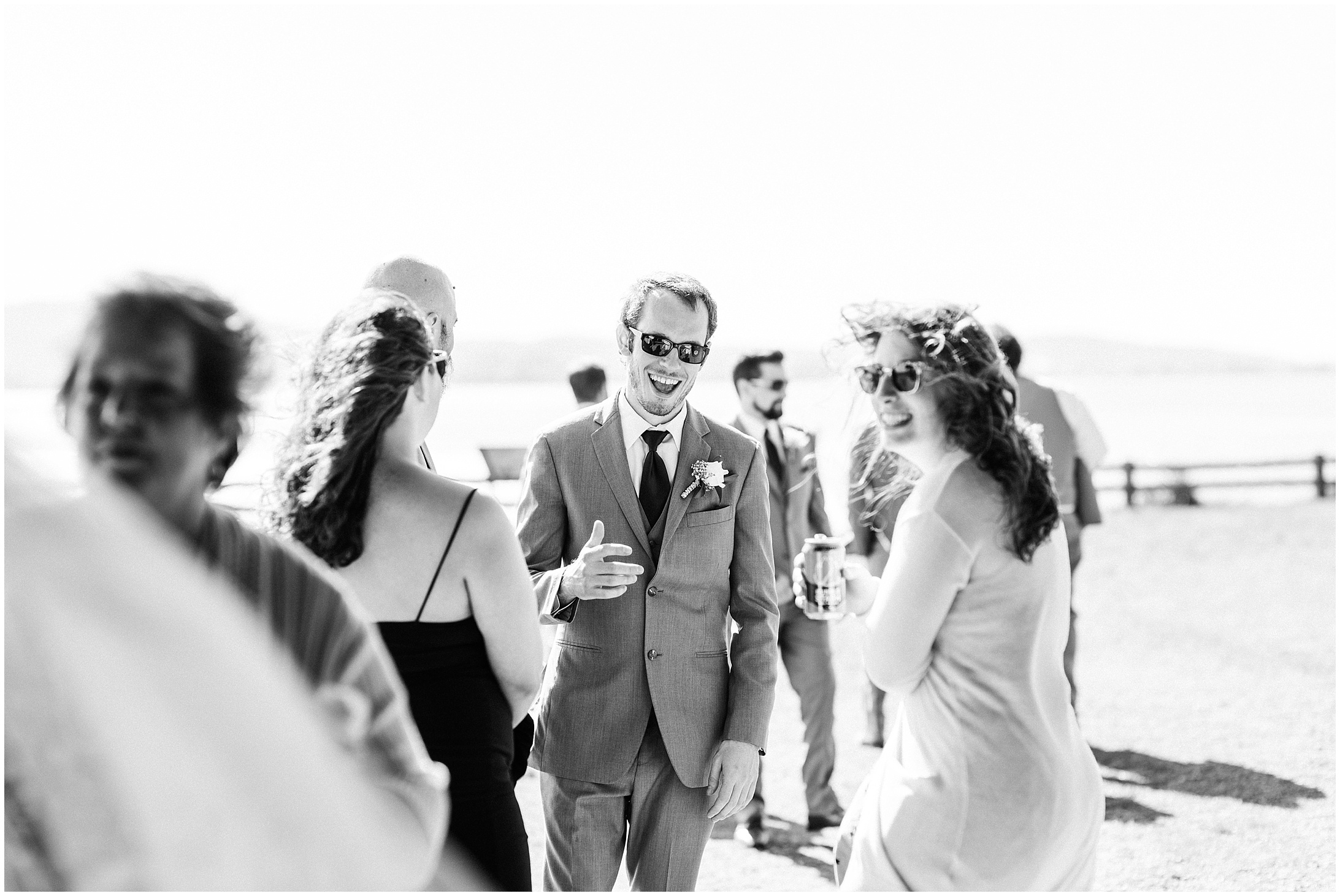 Black and white photo of wedding guests laughing in Bayview State Park