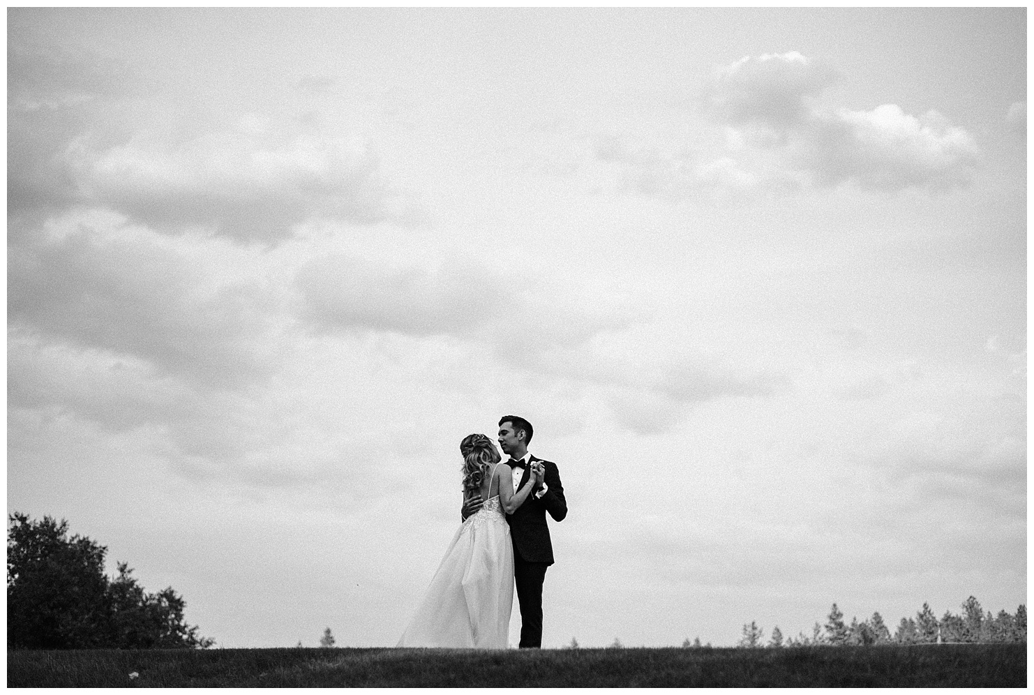 Black and white photo of a bride & groom dancing at sunset by Forthright Photo
