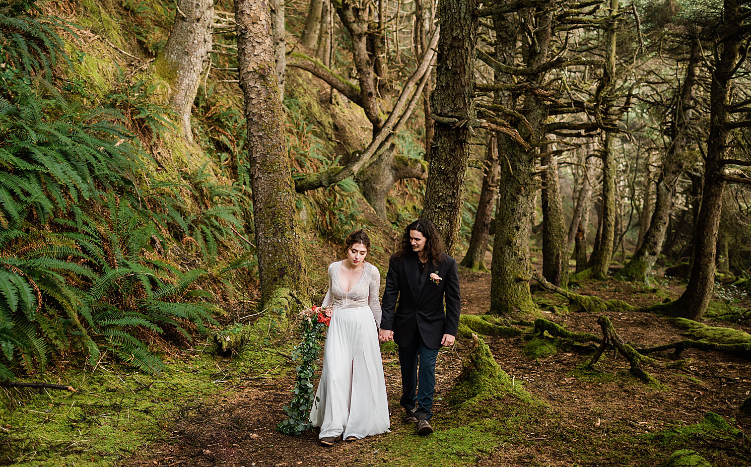 Bride and groom walking along the wooded Shi Shi beach trail. Image by Forthright Photo.