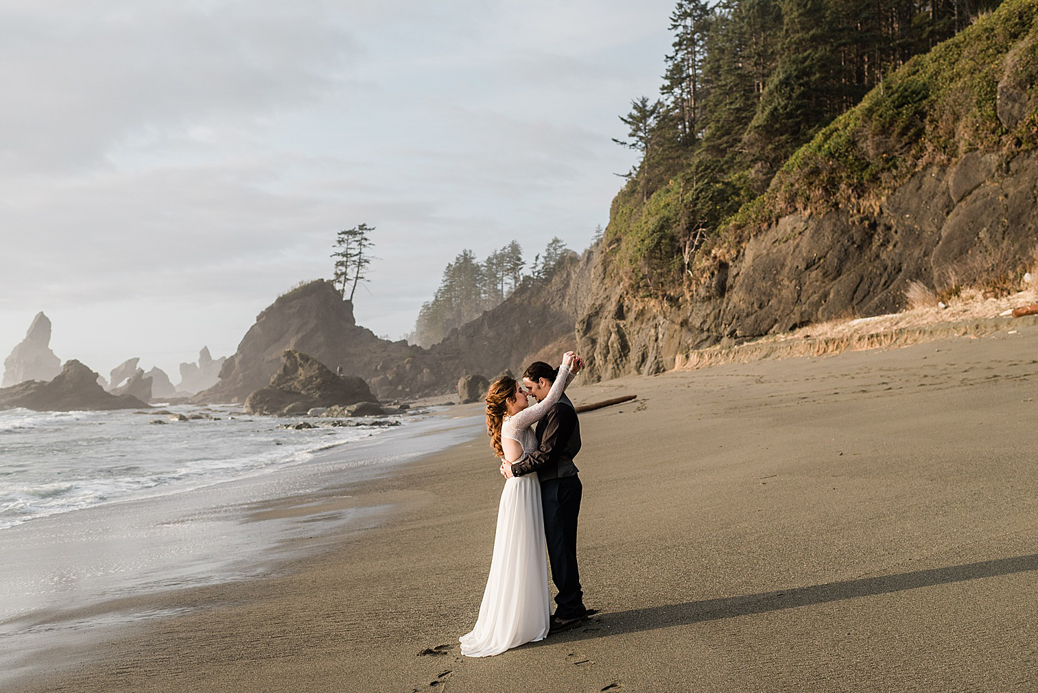 Olympic National Park Elopement Inspiration Shoot at Shi Shi Beach, bride & groom on the shoreline at sunset. Image by Forthright Photo.