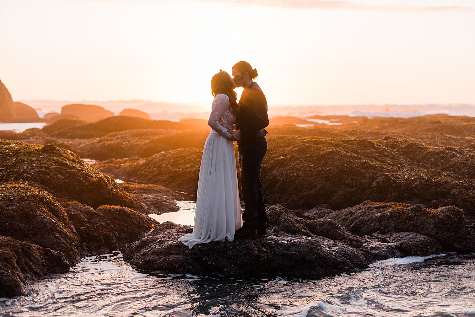 Bride and groom kissing at sunset on Shi Shi beach for their elopement. Image by Forthright Photo