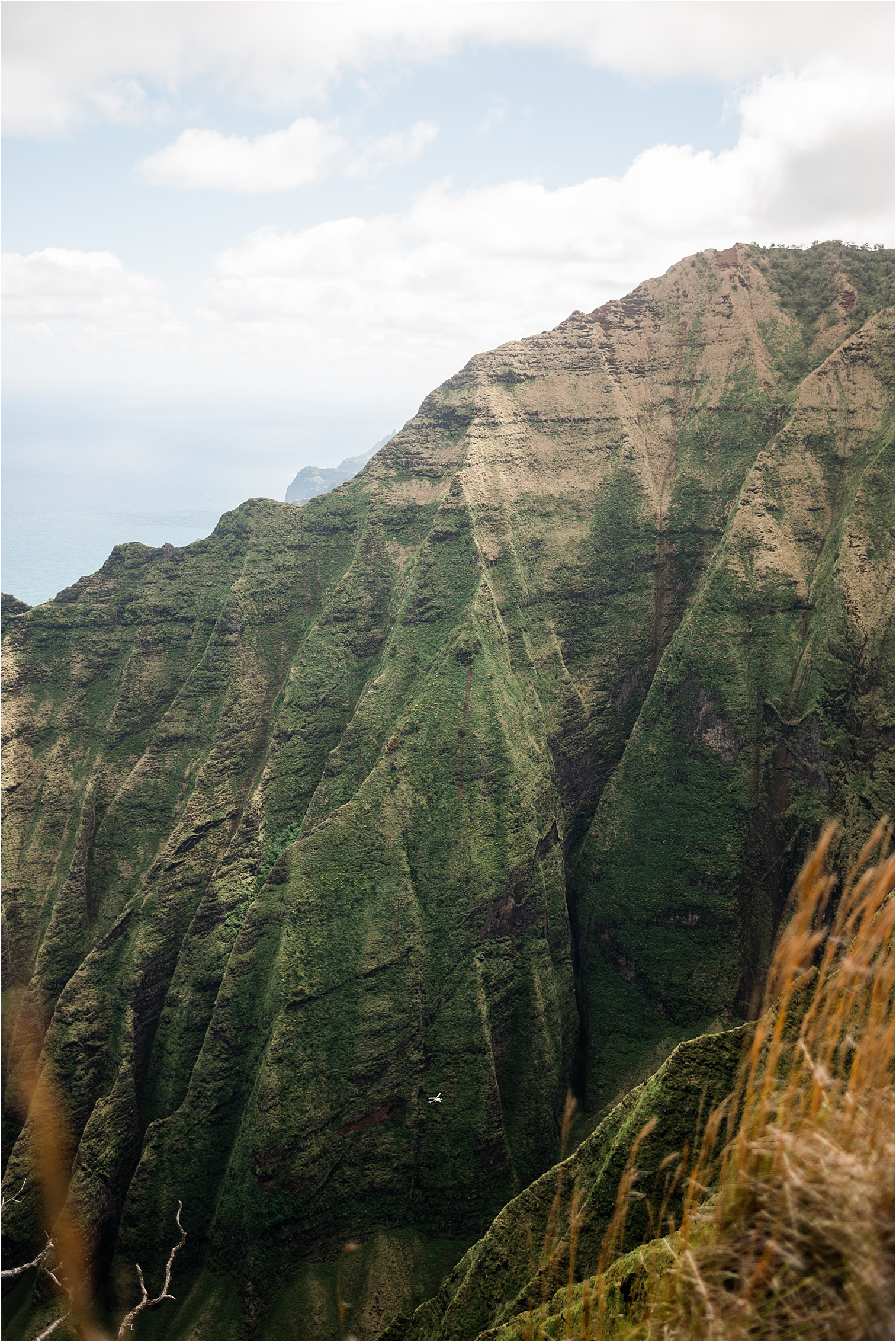 View of a Helicopter from the top of Honopu Ridge. Image by Forthright Photo, Kauai Adventure Wedding Photographers