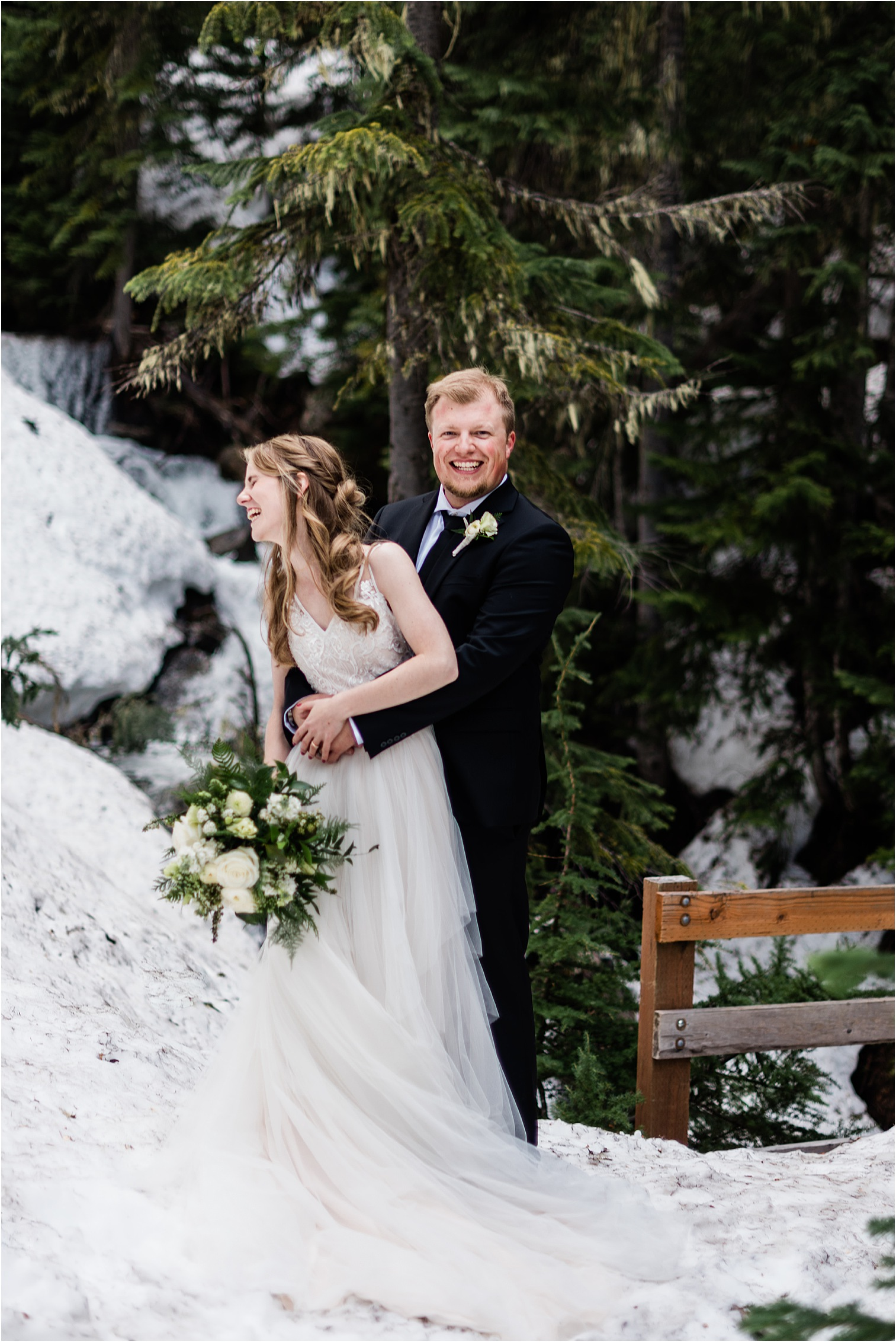 Hope & Steven laughing at a small waterfall bridge during their Adventure Wedding in the North Cascades. Image by Forthright Photo, Seattle Wedding & Elopement Photographers