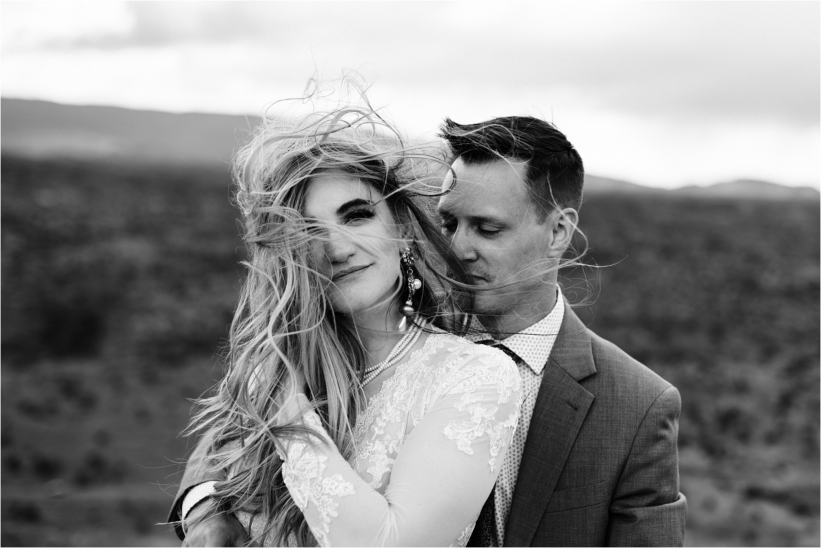 Close up wedding portrait of a bride with very wind blown hair. Image by Forthright Photo