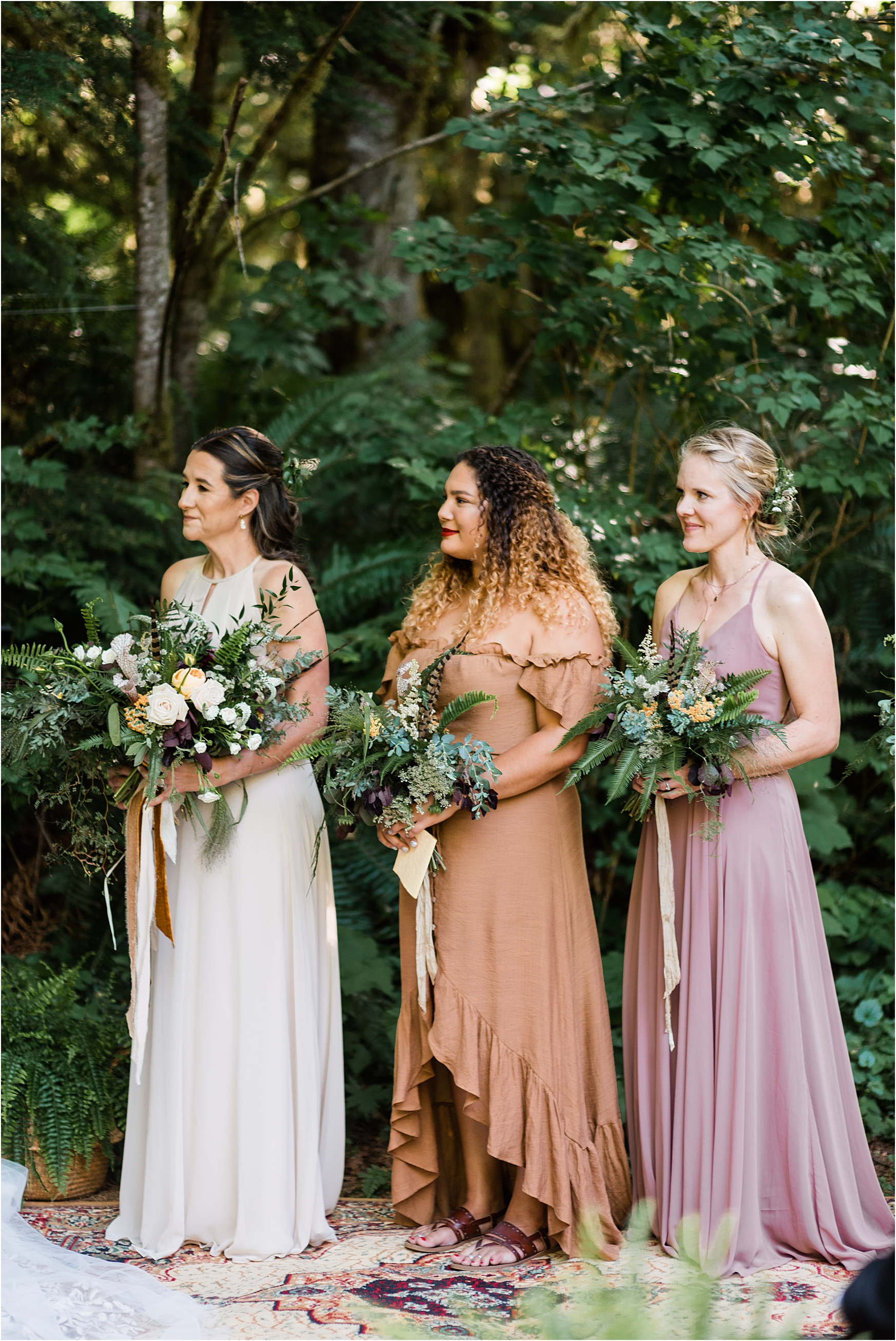 Bridesmaids during the ceremony at Cassy & Viva's bohemian Oregon destination wedding at Camp Lane. Image by Forthright Photo.