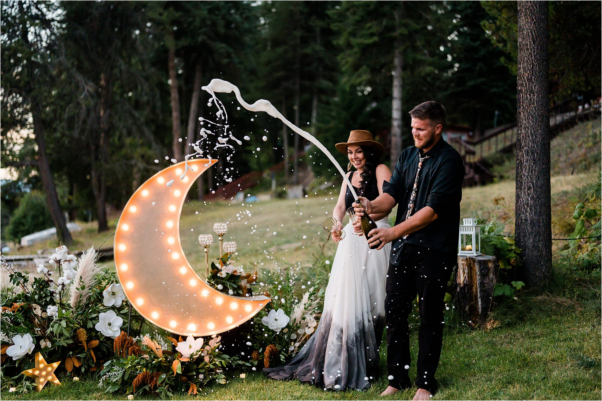 Shelby & Garrett popping some champagne at their backyard barbeque dinner on their elopement day. Image by Forthright Photo.