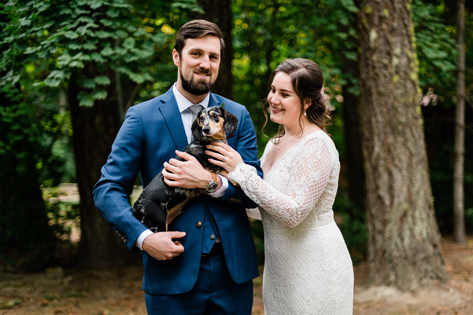 Jamie & Wilson's snuggle with their dachshund pup on their Leavenworth wedding day. Image by Forthright Photo, Seattle Wedding Photographers.